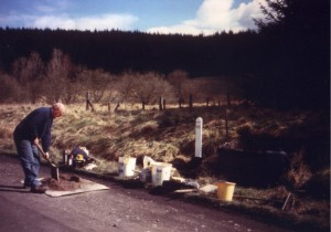 Len Ashton mixes concrete for setting milepost 66 in place just south of Riccarton Junction